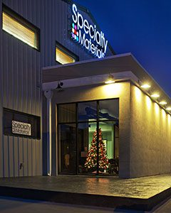 A Specialty Materials building during Christmas- there is a Christmas tree in the window