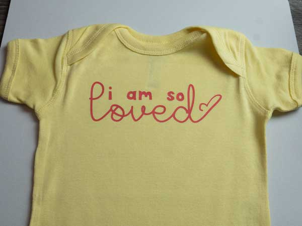 """The finished onesie, showing the words """"I am so loved"""" pressed onto a onesie in ThermoFlex Plus"""