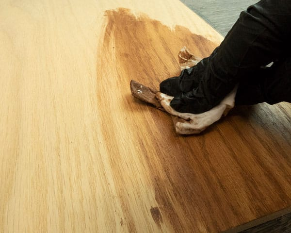A piece of wood being stained with a baby wipe and acrylic paint.