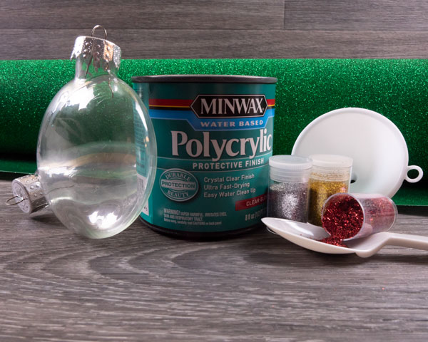 The supplies needed for this blog post- ornament, glitter, Pressure Sensitive GlitterFlex® Ultra, a funnel, and polycrylic