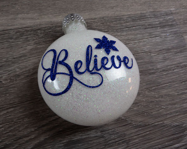 """A finished ornament with the word """"Believe"""" with white glitter on the inside using Pressure Sensitive GlitterFlex® Ultra"""
