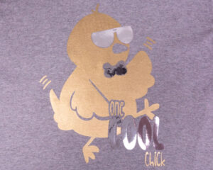 """A shirt with a chick in sunglasses and a bowtie that reads """"one cool chick"""" in Super Gold and Brilliant Silver DecoFilm"""